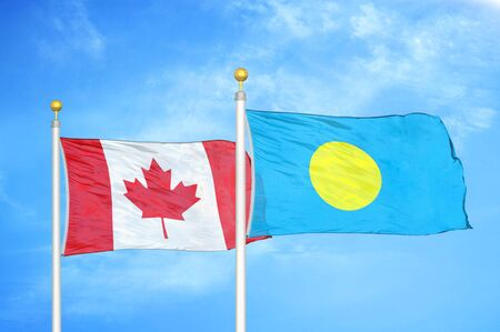 Canada and Palau two flags on flagpoles and blue cloudy sky background