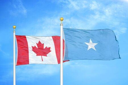 Canada and Somalia two flags on flagpoles and blue cloudy sky background
