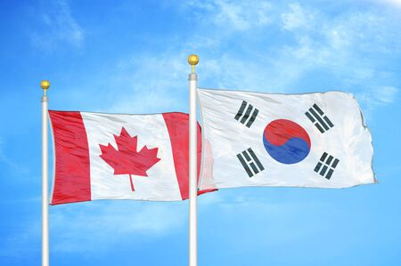 Canada and South Korea two flags on flagpoles and blue cloudy sky background