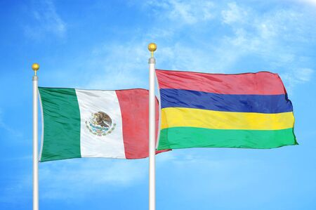 Mexico and Mauritius two flags on flagpoles and blue cloudy sky background