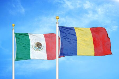 Mexico and Romania two flags on flagpoles and blue cloudy sky background Stock Photo