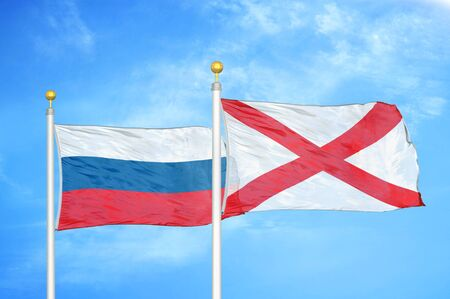 Russia and Northern Ireland two flags on flagpoles and blue cloudy sky background