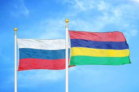 Russia and Mauritius two flags on flagpoles and blue cloudy sky background