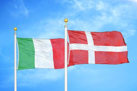 Italy and Denmark two flags on flagpoles and blue cloudy sky background Archivio Fotografico