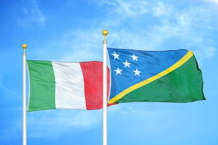 Italy and Solomon Islands two flags on flagpoles and blue cloudy sky background