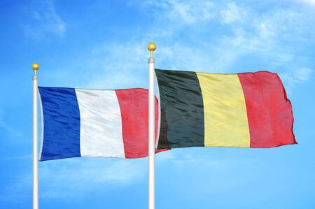 France and Belgium two flags on flagpoles and blue cloudy sky background 免版税图像