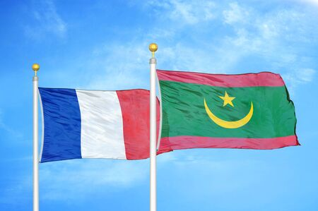 France and Mauritania two flags on flagpoles and blue cloudy sky background