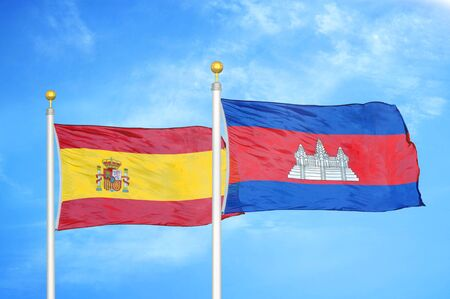 Spain and Cambodia  two flags on flagpoles and blue cloudy sky background Stock Photo