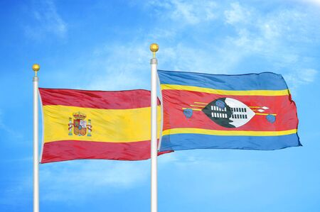 Spain and Eswatini Swaziland  two flags on flagpoles and blue cloudy sky background