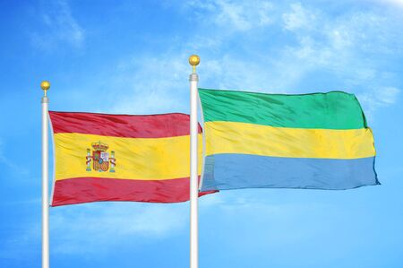 Spain and Gabon two flags on flagpoles and blue cloudy sky background