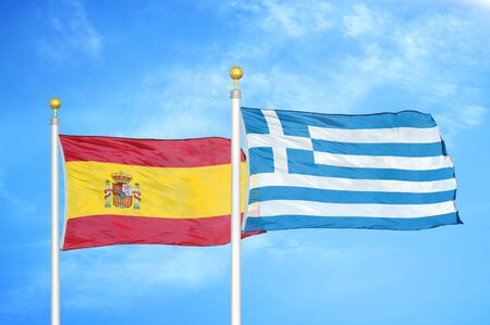 Spain and Greece two flags on flagpoles and blue cloudy sky background Standard-Bild