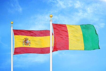 Spain and Guinea two flags on flagpoles and blue cloudy sky background Stock Photo
