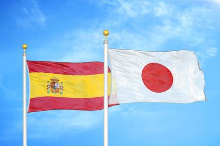 Spain and Japan two flags on flagpoles and blue cloudy sky background Stock Photo