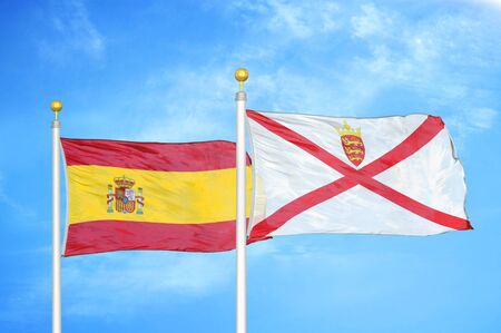 Spain and Jersey two flags on flagpoles and blue cloudy sky background Stock Photo
