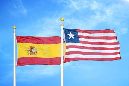Spain and Liberia two flags on flagpoles and blue cloudy sky background Stock Photo