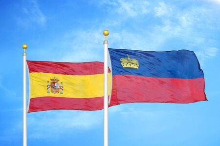 Spain and Liechtenstein two flags on flagpoles and blue cloudy sky background