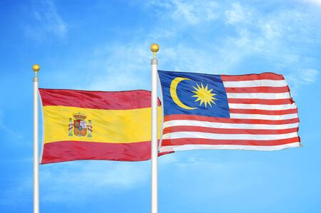 Spain and Malaysia two flags on flagpoles and blue cloudy sky background Stock Photo