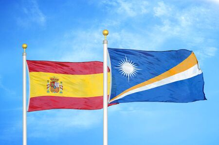 Spain and Marshall Islands two flags on flagpoles and blue cloudy sky background