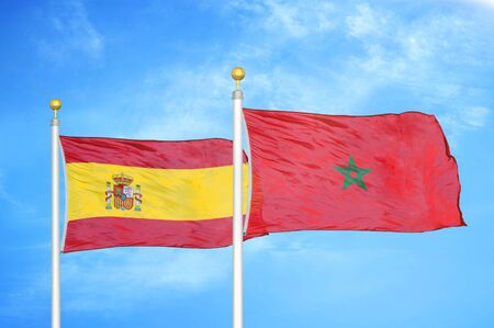 Spain and Morocco two flags on flagpoles and blue cloudy sky background