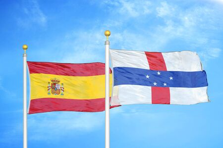 Spain and Netherlands Antilles two flags on flagpoles and blue cloudy sky background Stock Photo
