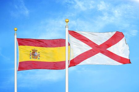 Spain and Northern Ireland two flags on flagpoles and blue cloudy sky background Banque d'images