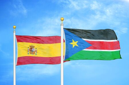 Spain and South Sudan two flags on flagpoles and blue cloudy sky background Stock Photo