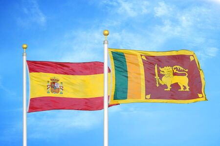 Spain and Sri Lanka two flags on flagpoles and blue cloudy sky background