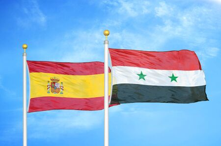 Spain and Syria two flags on flagpoles and blue cloudy sky background