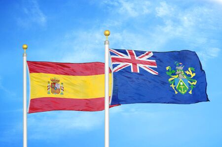 Spain and Pitcairn Islands two flags on flagpoles and blue cloudy sky background