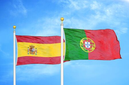 Spain and Portugal two flags on flagpoles and blue cloudy sky background