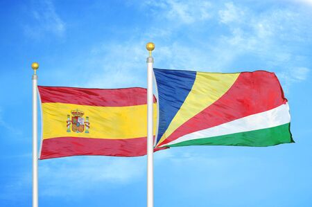 Spain and Seychelles two flags on flagpoles and blue cloudy sky background