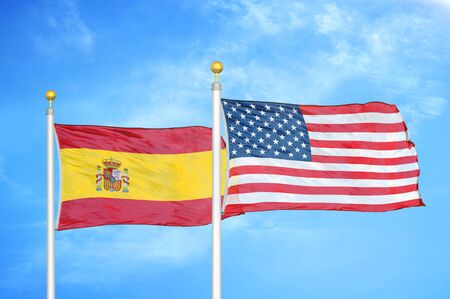 Spain and United States two flags on flagpoles and blue cloudy sky background
