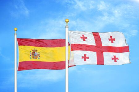 Spain and Georgia two flags on flagpoles and blue cloudy sky background