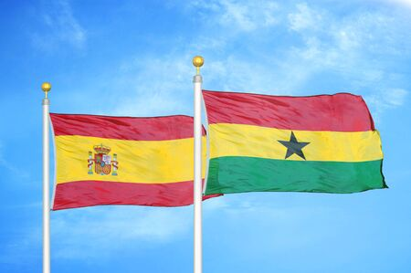 Spain and Ghana two flags on flagpoles and blue cloudy sky background Stock Photo