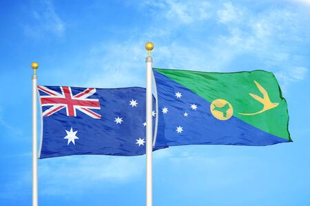 Australia and Christmas Island two flags on flagpoles and blue cloudy sky background Stock Photo
