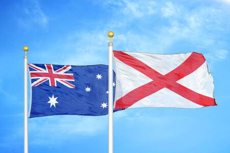 Australia and Northern Ireland two flags on flagpoles and blue cloudy sky background Banque d'images