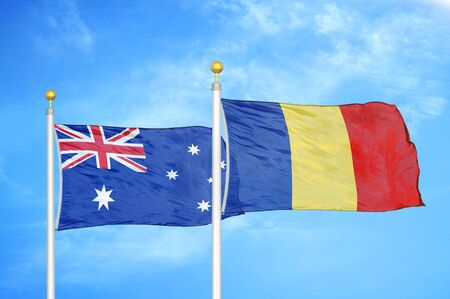 Australia and Romania two flags on flagpoles and blue cloudy sky background