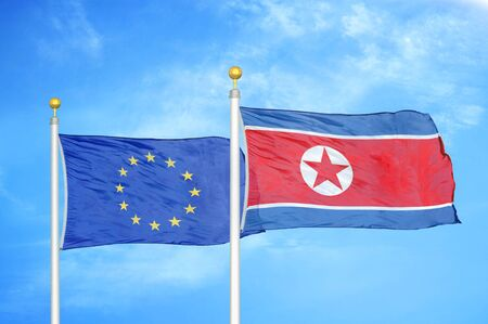 European Union and North Korea two flags on flagpoles and blue cloudy sky background