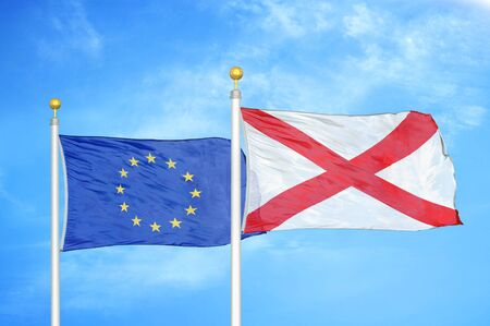 European Union and Northern Ireland two flags on flagpoles and blue cloudy sky background