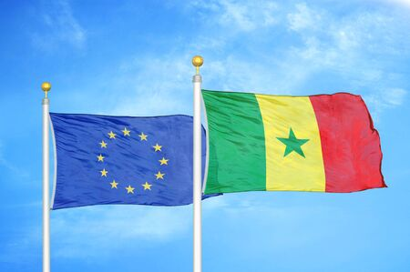 European Union and Senegal two flags on flagpoles and blue cloudy sky background