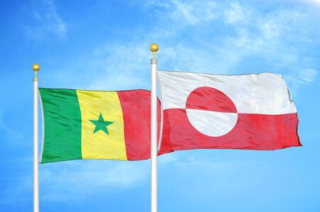 Senegal and Greenland two flags on flagpoles and blue cloudy sky background