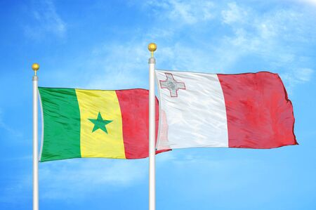 Senegal and Malta two flags on flagpoles and blue cloudy sky background Stock Photo