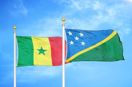 Senegal and Solomon Islands two flags on flagpoles and blue cloudy sky background Stock Photo