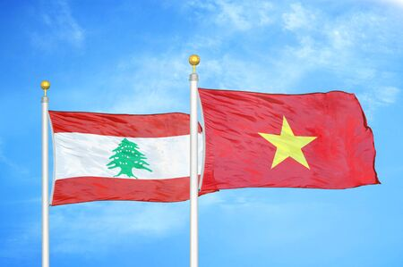 Lebanon and Vietnam two flags on flagpoles and blue cloudy sky background Stock Photo
