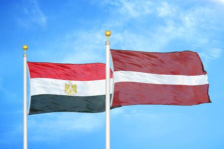Egypt and Latvia two flags on flagpoles and blue cloudy sky background 版權商用圖片