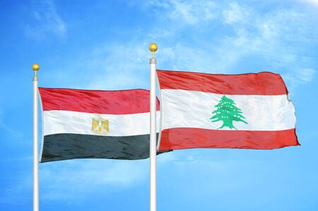 Egypt and Lebanon two flags on flagpoles and blue cloudy sky background