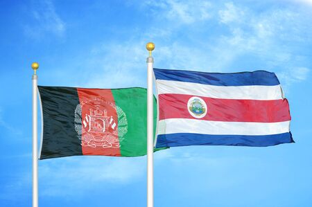 Afghanistan and Costa Rica  two flags on flagpoles and blue cloudy sky background