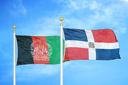 Afghanistan and Dominican Republic  two flags on flagpoles and blue cloudy sky background