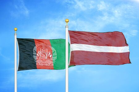 Afghanistan and Latvia  two flags on flagpoles and blue cloudy sky background