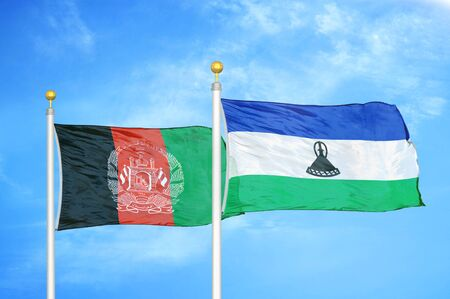 Afghanistan and Lesotho  two flags on flagpoles and blue cloudy sky background 版權商用圖片